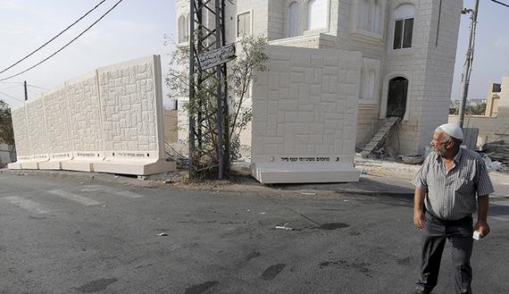 Un palestinese cammina nei pressi di un muro provvisorio in cemento, appena costruito nel quartiere di Jabel Mukaber, a Gerusalemme est. 19 ottobre  2015 (foto REUTERS/Ammar Awad)