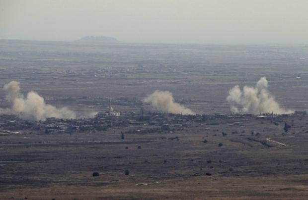 """Una foto presa dalle annesse Alture del Golan il 10 settembre 2016 mostra del fumo che s'innalza dal villaggio siriano . Jubata al-Khashab. Gli aerei israeliani hanno colpito le posizioni dell'esercito siriano il 10 di settembre dopo che dal devastato vicino Siria un proiettile ha colpito la zona delle alture del Golan occupate da Israele; secondo quanto detto dai militari israeliani in un comunicato dell'esercito  l'incursione ha preso di mira le posizioni dell'artiglieria del regime siriano in risposta a """"un proiettile"""" che ha colpito la parte settentrionale del Golan, non causando  feriti e neanche danni. /AFP foto /Jalaa Marey"""