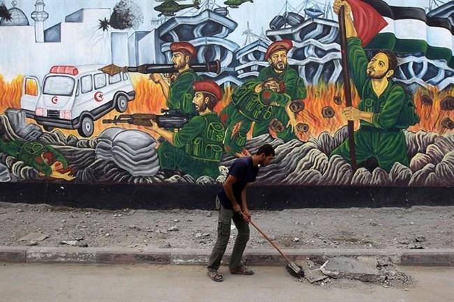 Un lavoratore palestinese pulisce la strada davanti ad un mural di guerra nei pressi del quartier generale Al-Saraya di Hamas a Gaza city - 22 novembre 2012 (AFP/Mahmud Hams, File)